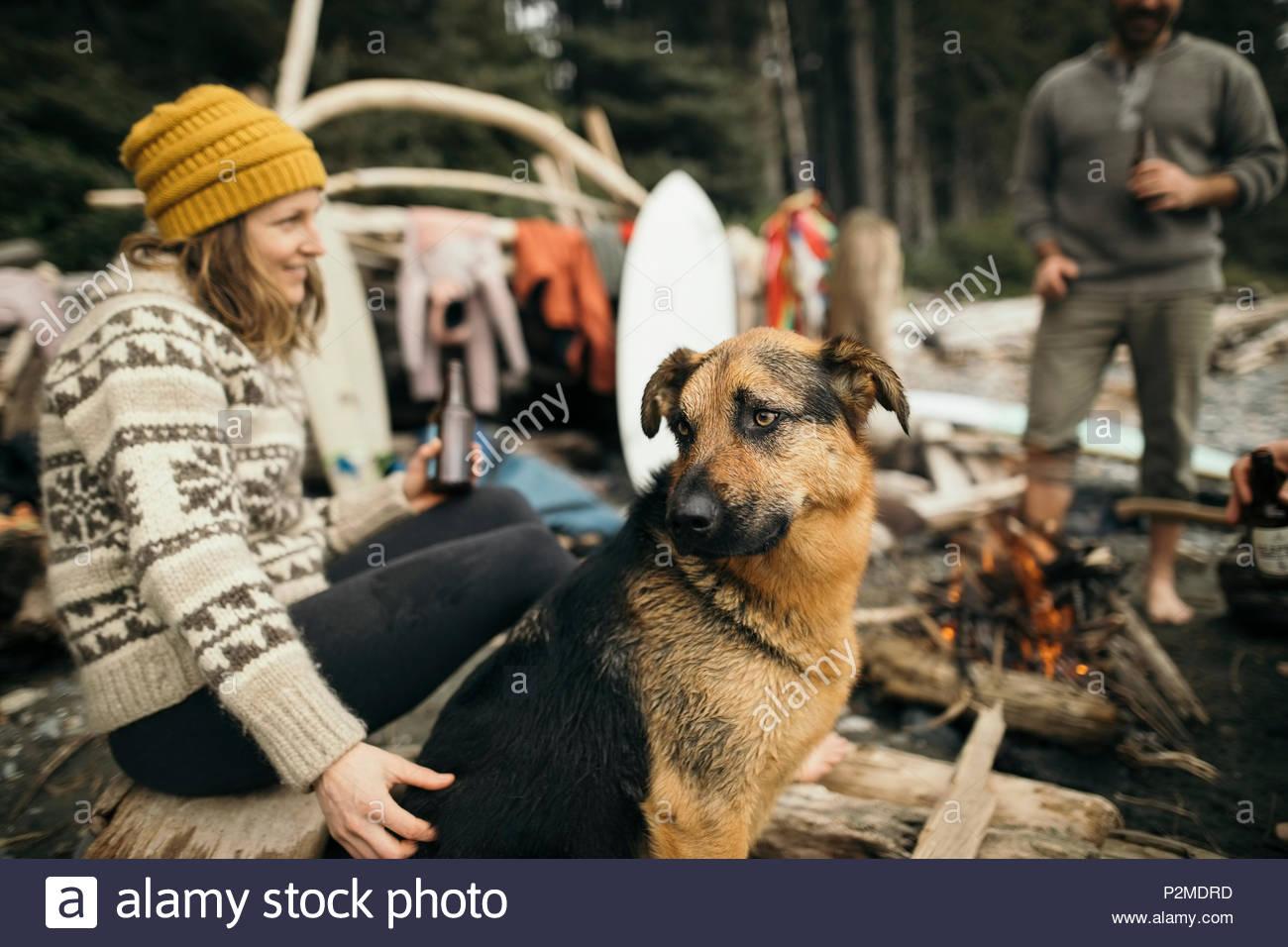 Mujer con perro disfruta de una escapada de fin de semana de surf, relajante en la fogata Foto de stock