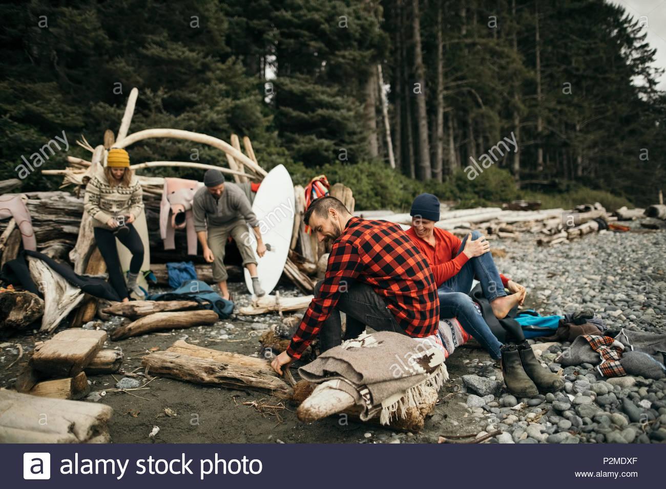Amigos, disfrutando de una escapada de fin de semana de surf, relajándose en la playa de camping en los robustos Imagen De Stock