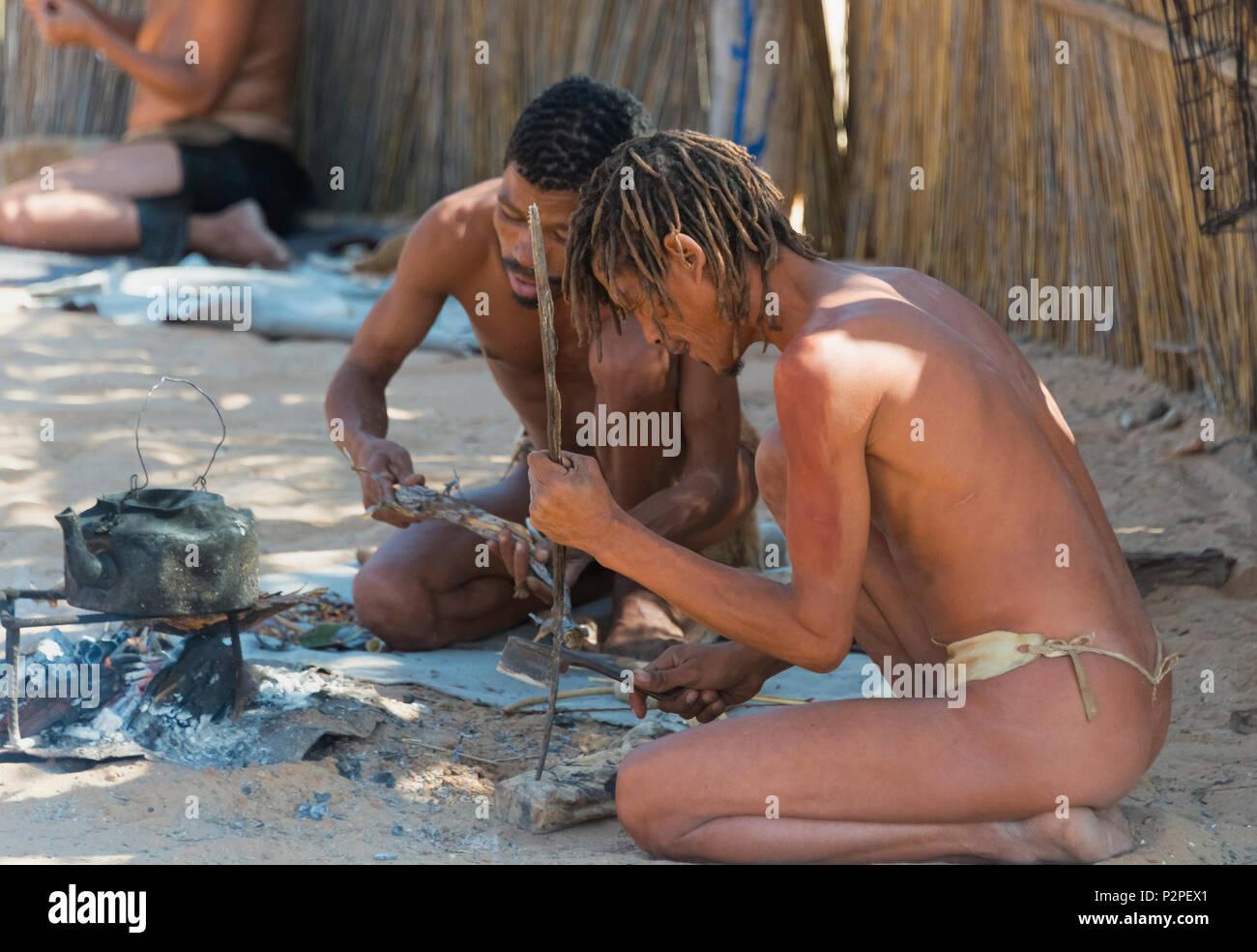 Bushman utilizando huesos de animales para hacer joyas en la aldea, el Parque Transfronterizo Kgalagadi, Sudáfrica Imagen De Stock