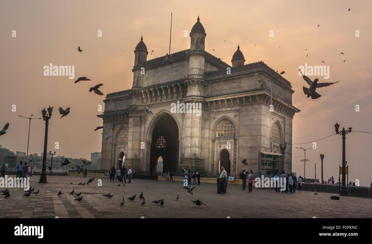 MUMBAI, India - 14 de enero de 2017, personas no identificadas a pie y palomas vuelan alrededor de la puerta de la India Imagen De Stock