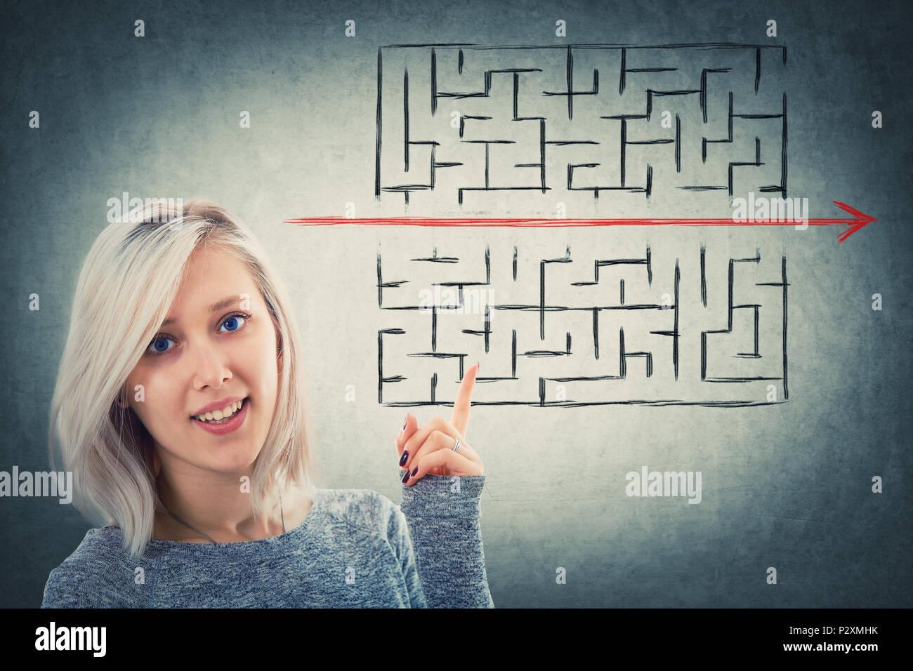 Close Up retrato de un desconcertado mujer señalando su dedo hacia arriba mostrando una solución para escapar del laberinto. Joven Empresaria romper las reglas, como Imagen De Stock