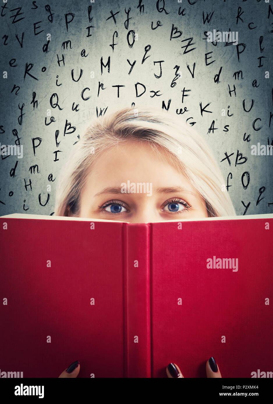 Close Up retrato de pretty girl estudiante rojo escondiéndose detrás de un libro abierto con las letras del alfabeto relativos en el fondo. Misteriosa y tímida mujer mantenga Imagen De Stock