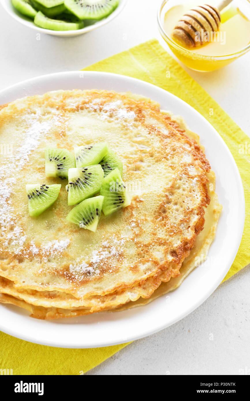 Crepes caseras decoradas con rodajas de kiwi. Los pancakes. Imagen De Stock