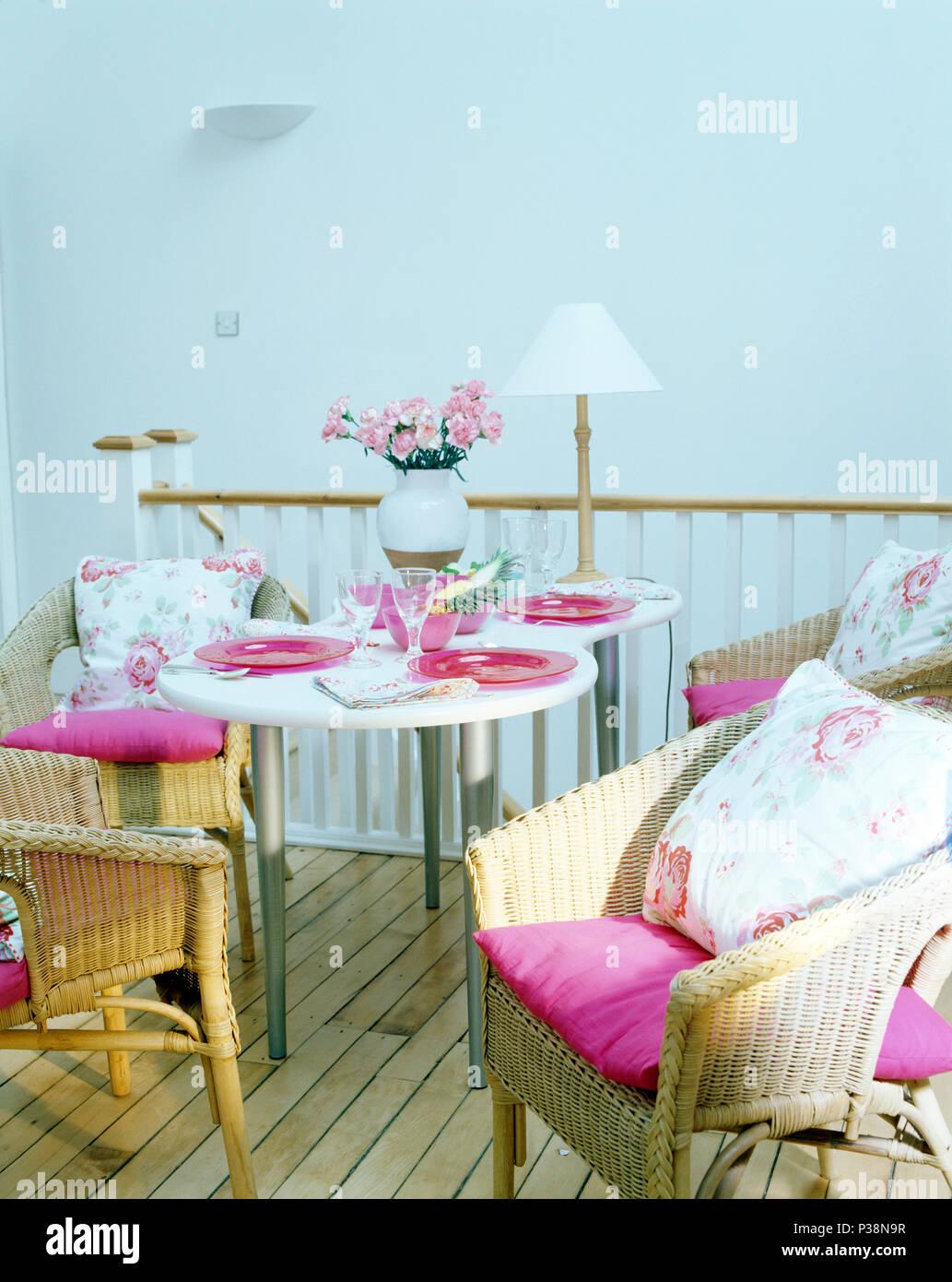 Rosa y cojines florales en sillas de mimbre en una mesa ...