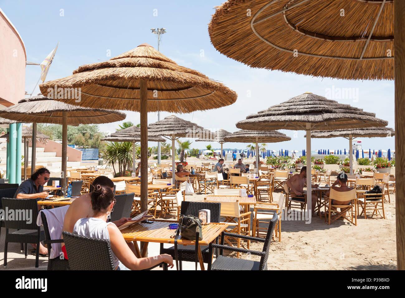 Pizzería Blue Moon, Luna Azul Beach, Lido di Venezia, Venecia, Véneto, Italia. Gente comiendo bajo sombrillas de paja en primavera tardía, atracción turística Foto de stock