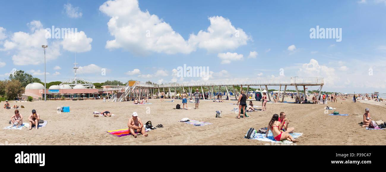 Panorama de Luna Azul Beach, Lido di Venezia, Venecia, Véneto, Italia a fines de la primavera con el muelle y restaurantes, gente nadar y tomar el sol Foto de stock