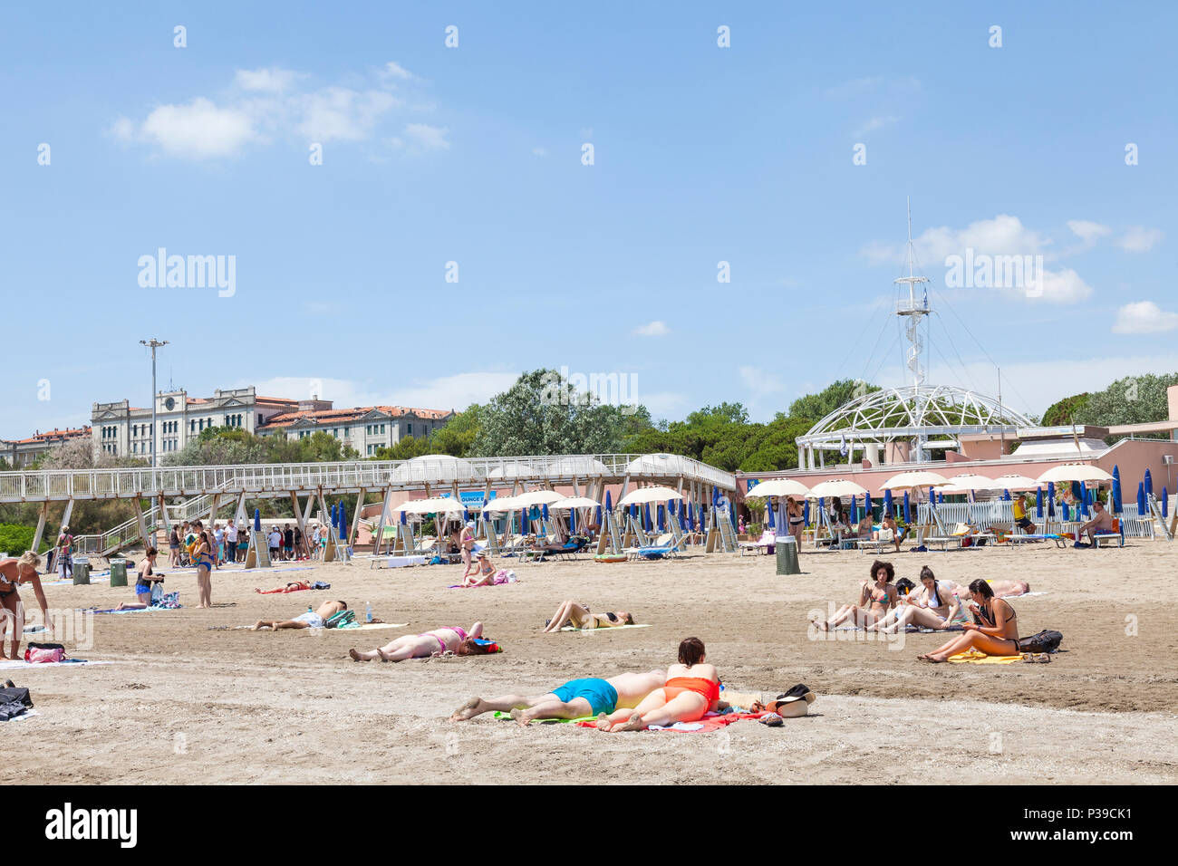 Las personas tomando el sol en la playa de Blue Moon, Lido di Venezia, a la Isla de Lido, Venecia, Véneto, Italia, en un soleado día de finales de primavera. Pier, restaurantes, observación Foto de stock