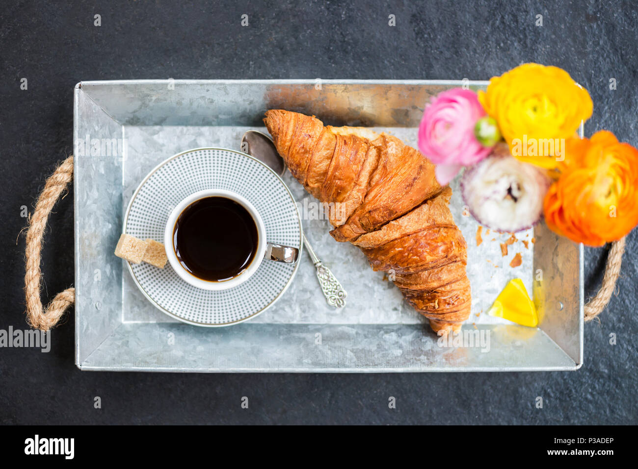 Desayuno ligero desde croissants frescos y una taza de café en la bandeja gris, Ranunculus flores cerca Foto de stock