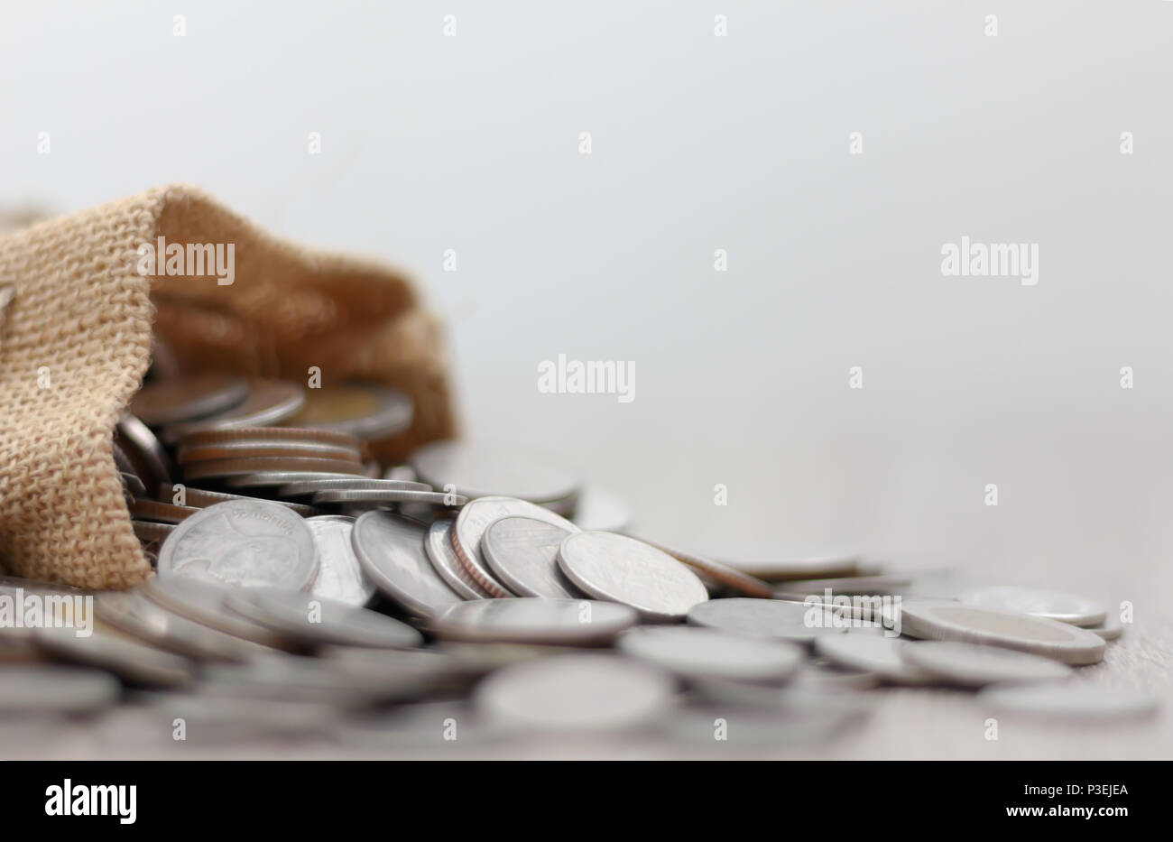 Monedas en el saco sobre la mesa de madera con espacio de copia. Seleccione focus gran profundidad de campo y el fondo borroso. Foto de stock
