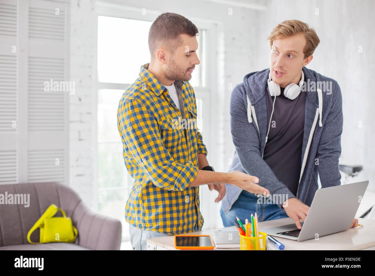 Los colegas masculinos positivos informe cambiante Imagen De Stock