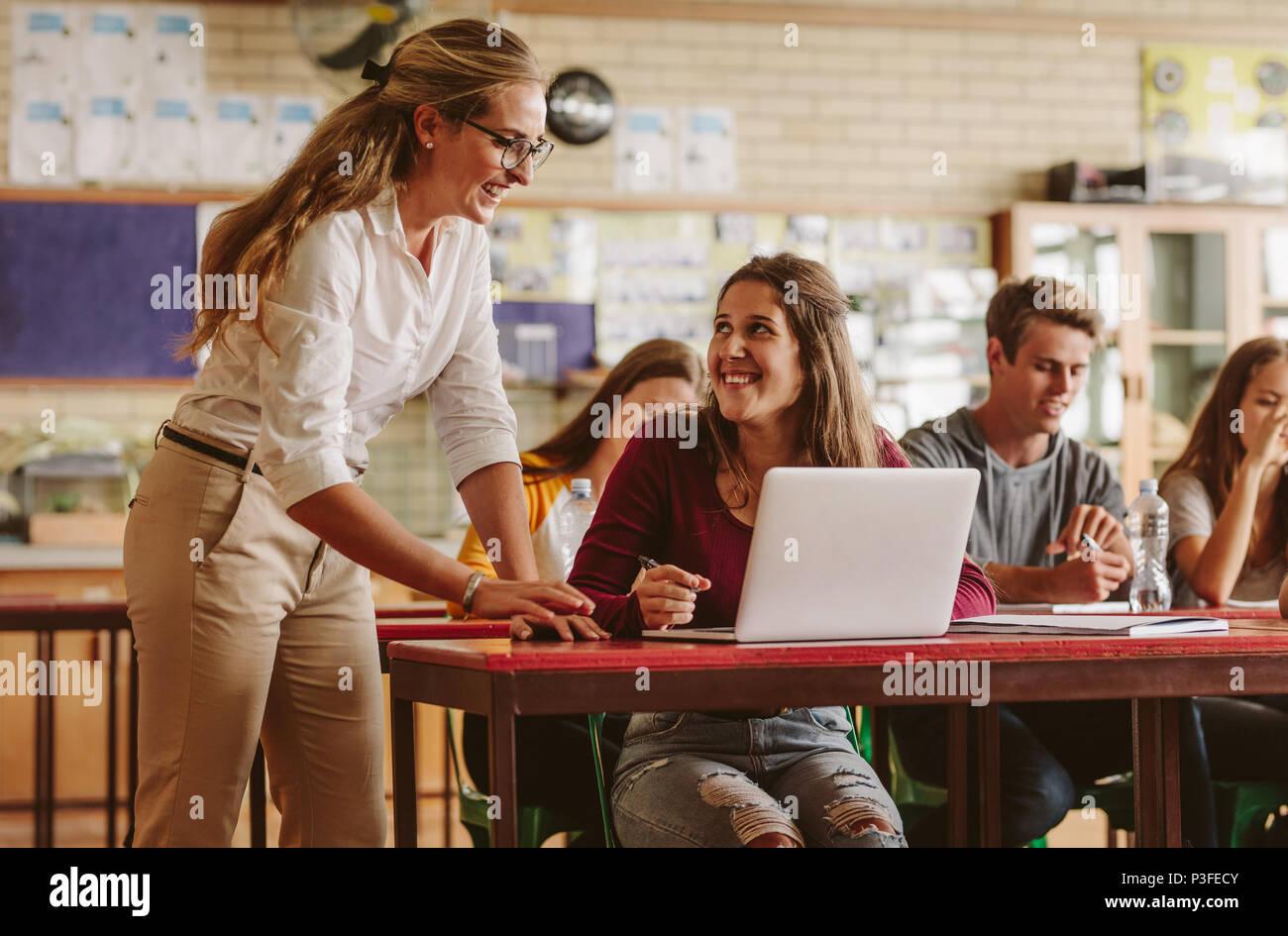 Profesor de la escuela de alta mujer feliz ayudando a los estudiantes durante su clase. Grupo de jóvenes en el aula con el amable maestro. Imagen De Stock