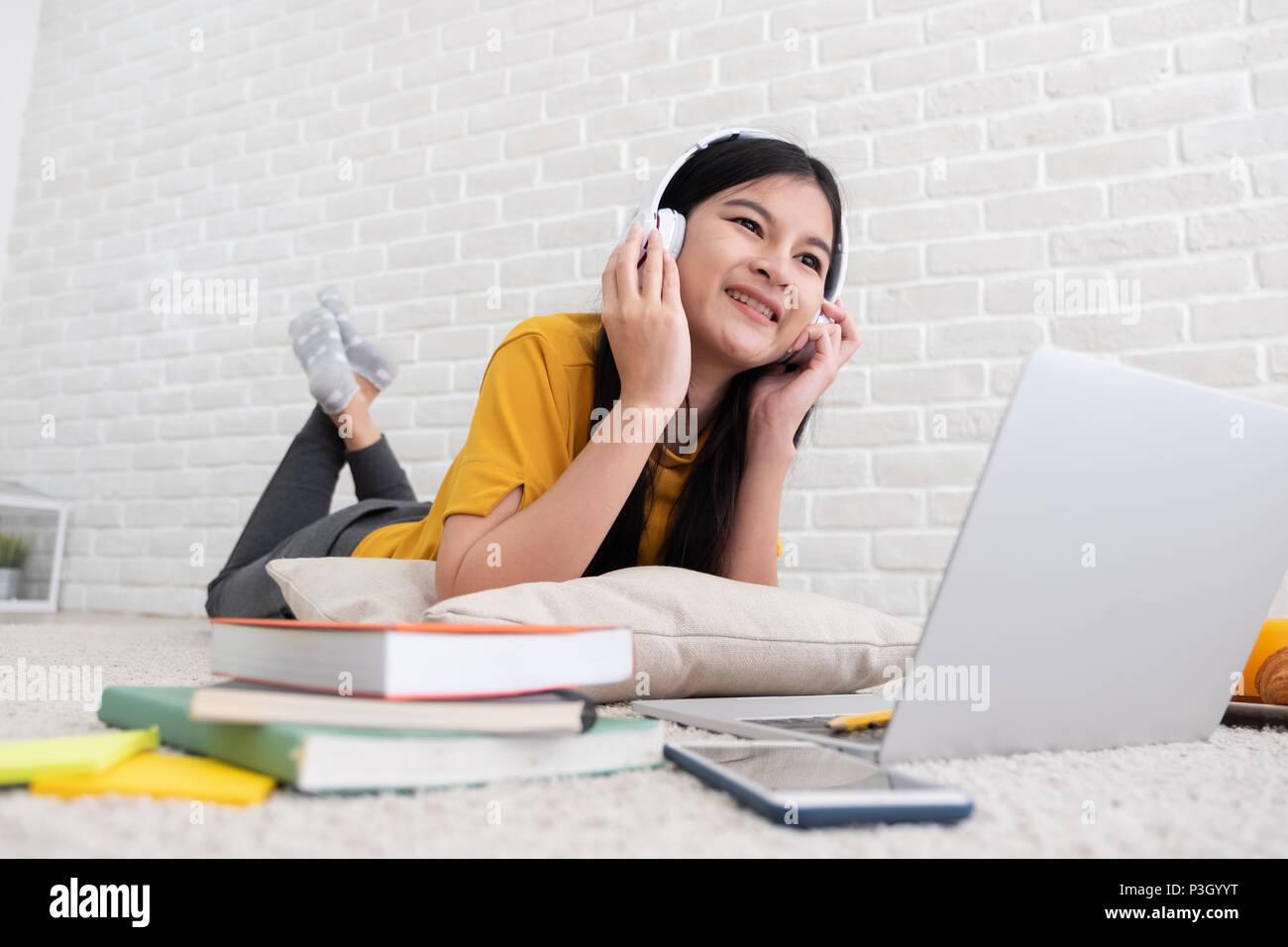 Mujeres asiáticas escuchar música y usar equipo portátil para trabajar en casa.mujer sentar sobre una alfombra de pared de ladrillo.trabajo estilo de vida online Imagen De Stock