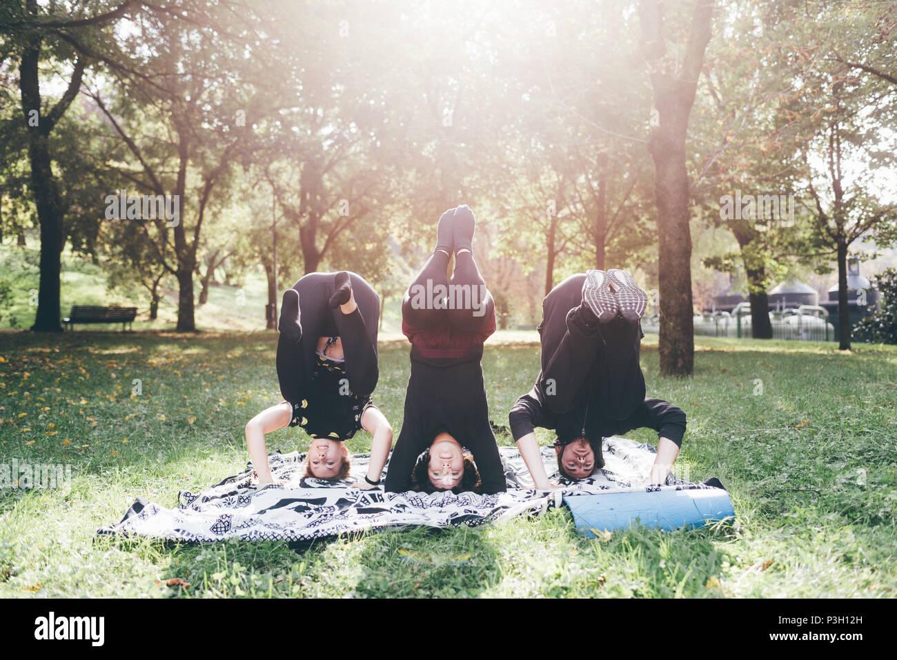 Los jóvenes hombres y mujeres de estiramiento en un parque de la ciudad al aire libre en días soleados, deportivo, formación, concepto wellness Imagen De Stock