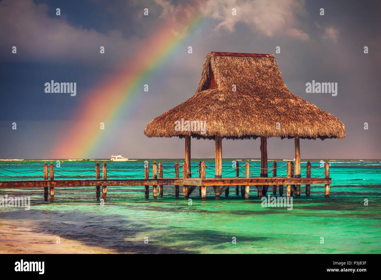 Arco iris sobre el agua de madera Villa en Cap Cana, República Dominicana. Imagen De Stock