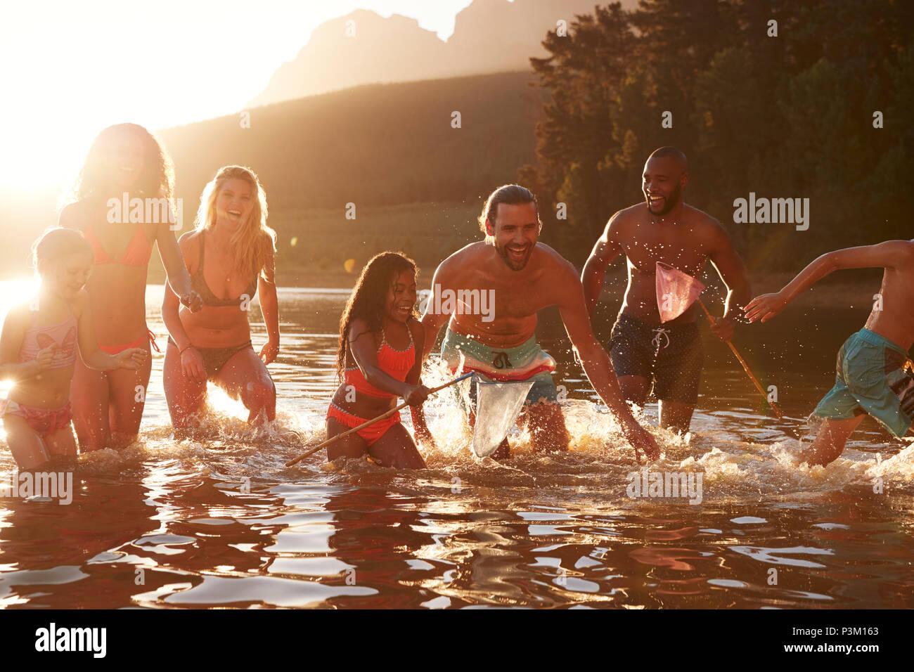 Familia con amigos, disfrutando de la noche nadar en el lago de la Campiña Imagen De Stock