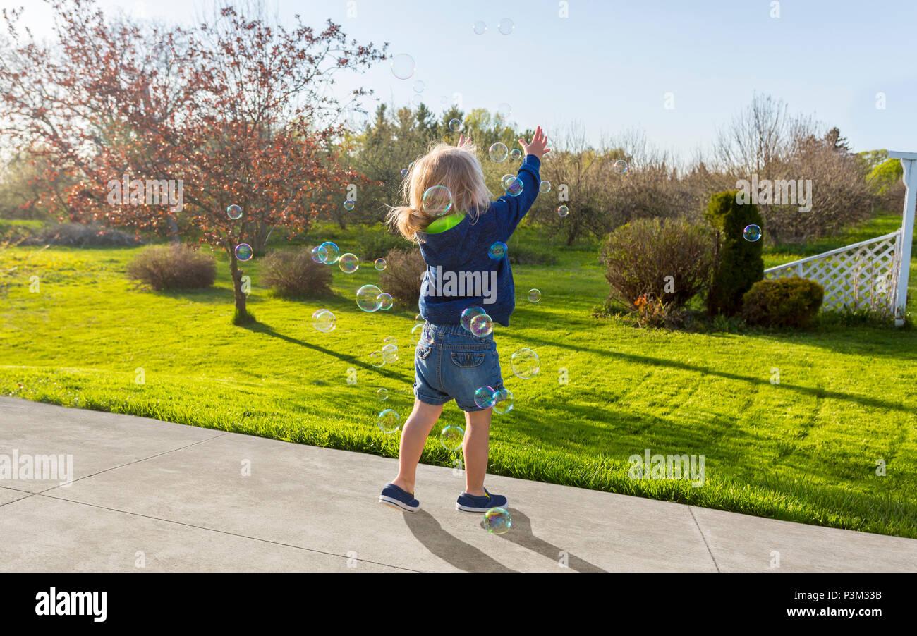 Caucasian andar jugando con pompas de jabón en el exterior Imagen De Stock