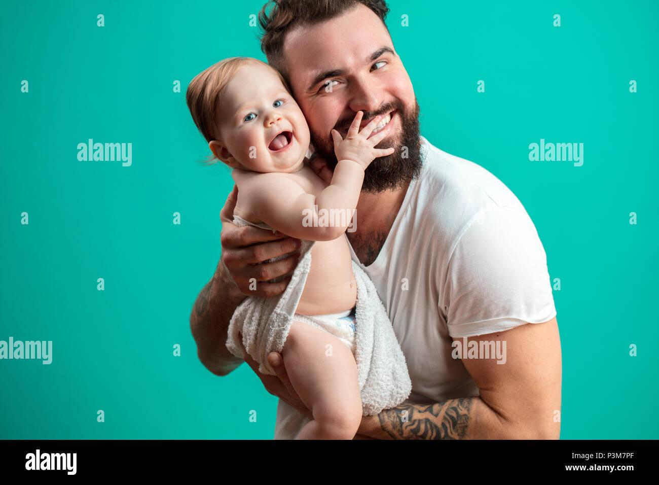 Juguetón padre llevar a su niño sonriente en cuello sobre fondo azul. Imagen De Stock