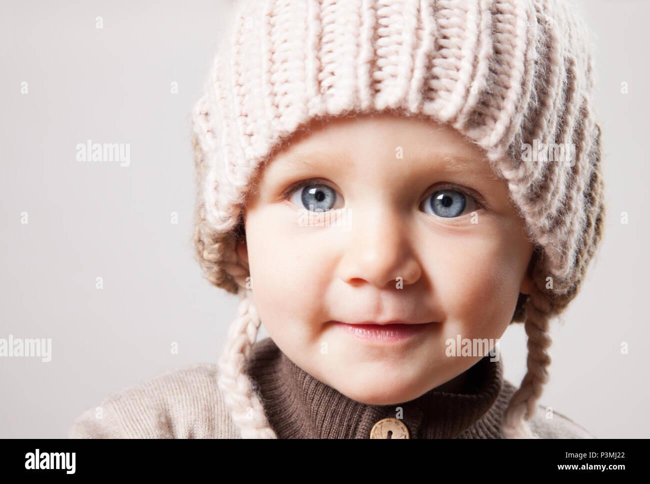 Retrato de un lindo bebé niña en un enorme gorro de punto marrón. Aislado  sobre a856ae19f1c