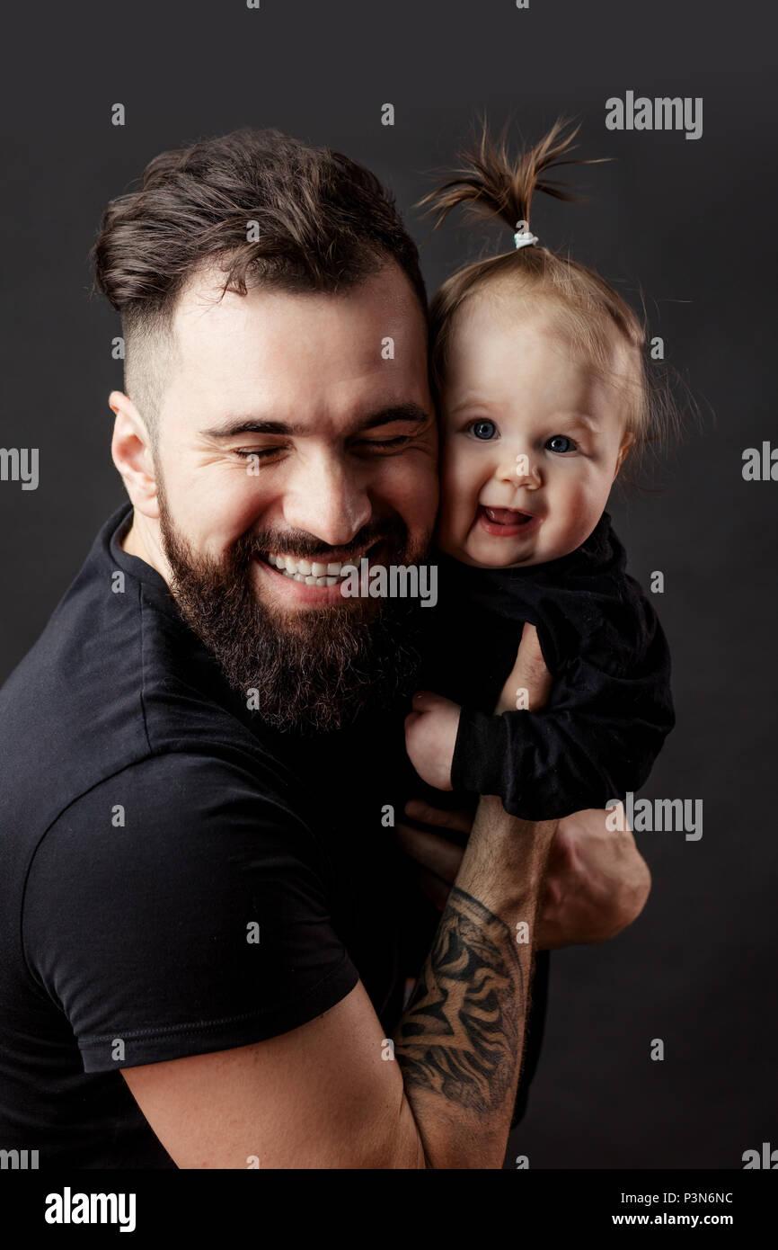 Apuesto joven tatuado celebración cute little baby sobre fondo negro Imagen De Stock