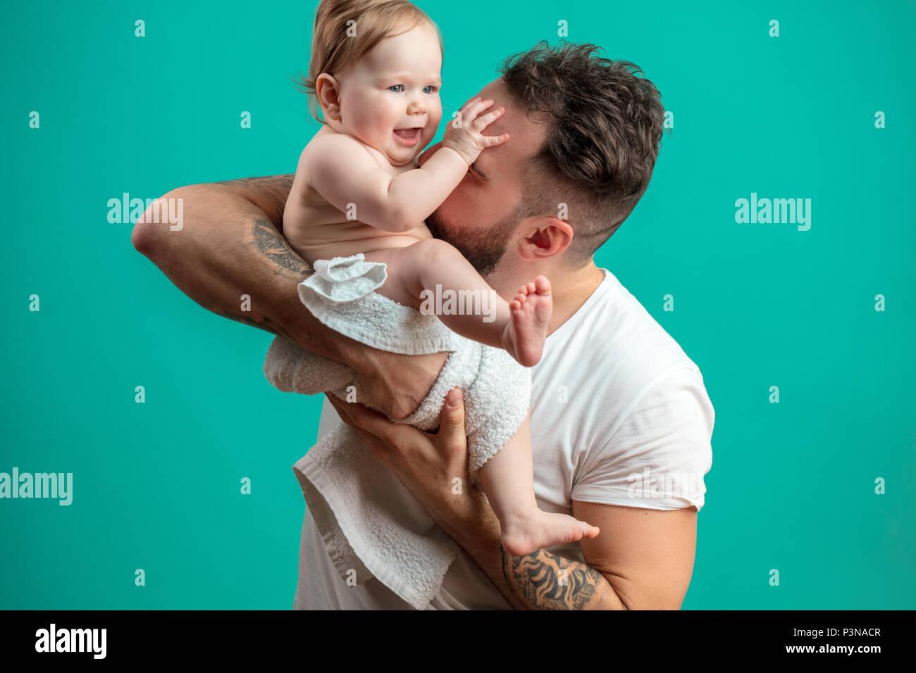 Juguetón padre llevar a su niño sonriente en cuello sobre fondo azul. Foto de stock