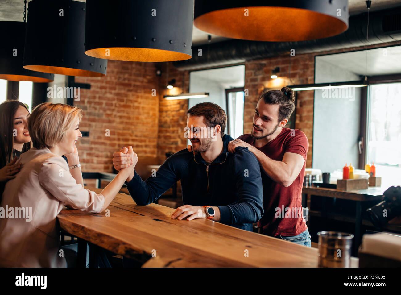 Gyu alegre y divertirse chica arm wrestling mutuamente en el pub. Imagen De Stock