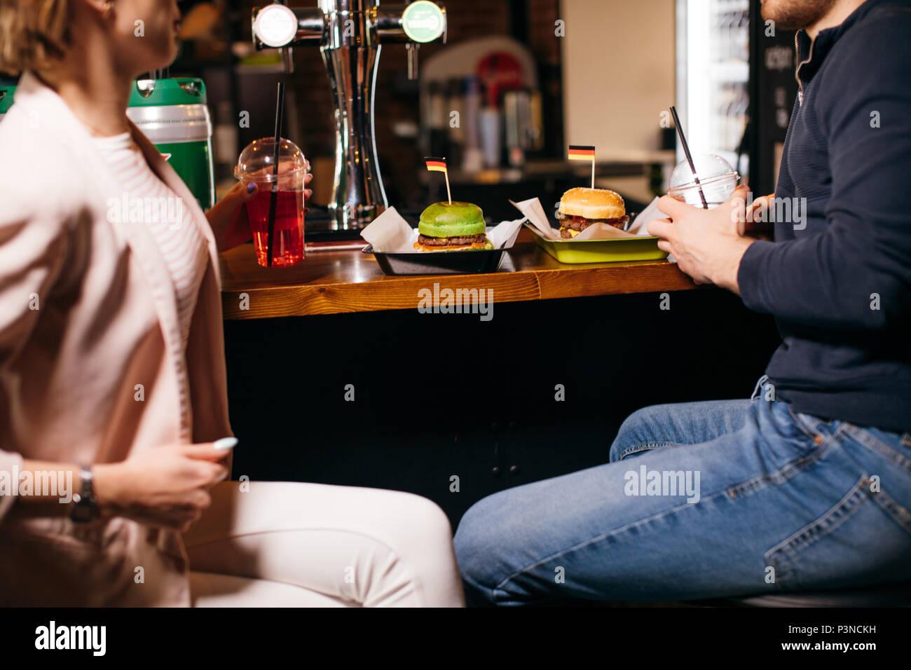 Grupo de jóvenes sentados en un café, conversar y disfrutar Imagen De Stock