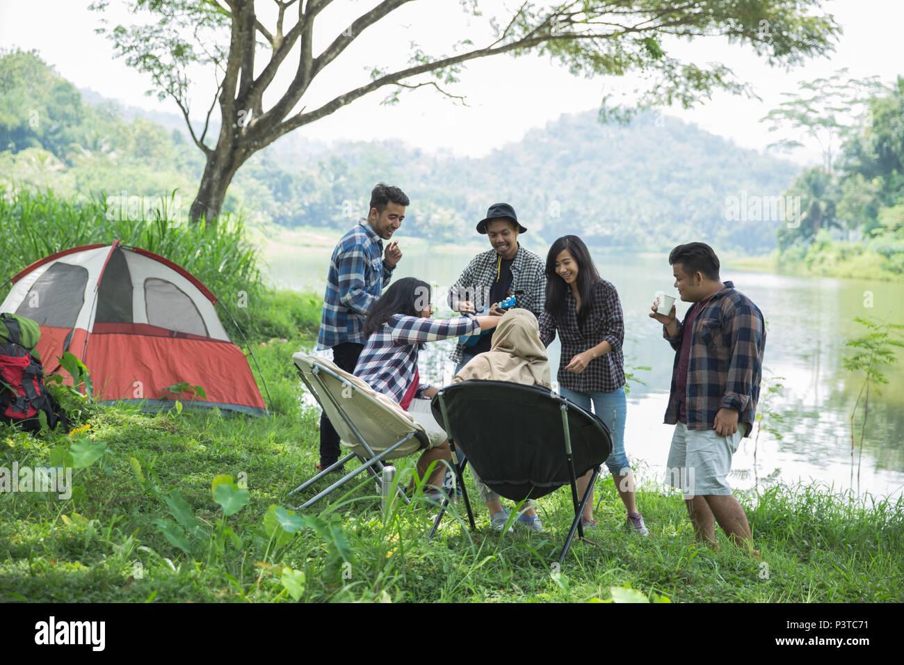 Amigos relajándose fuera de carpas en camping Imagen De Stock