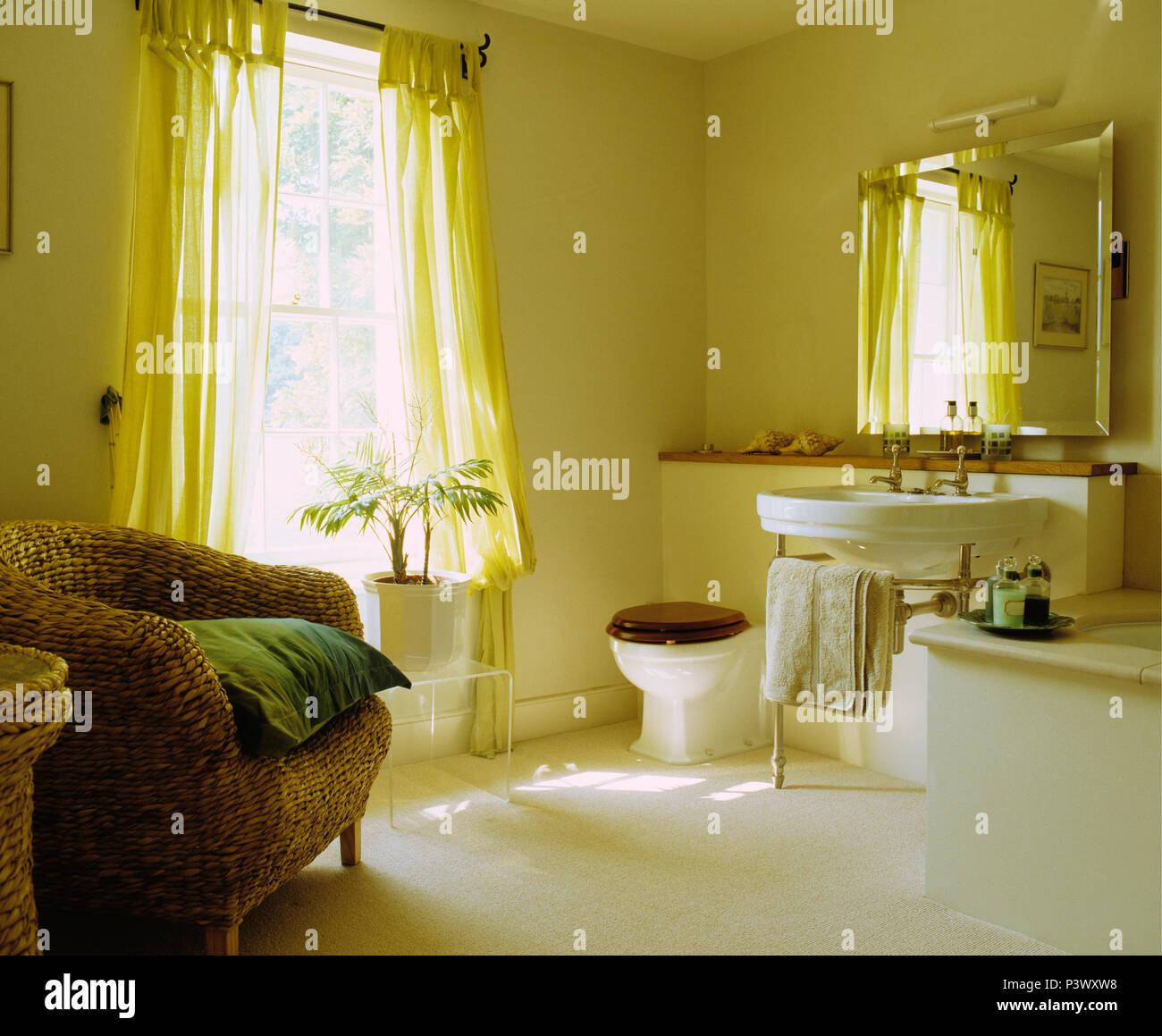 Gran cuarto de baño tradicional con silla de mimbre y cortinas Foto ...