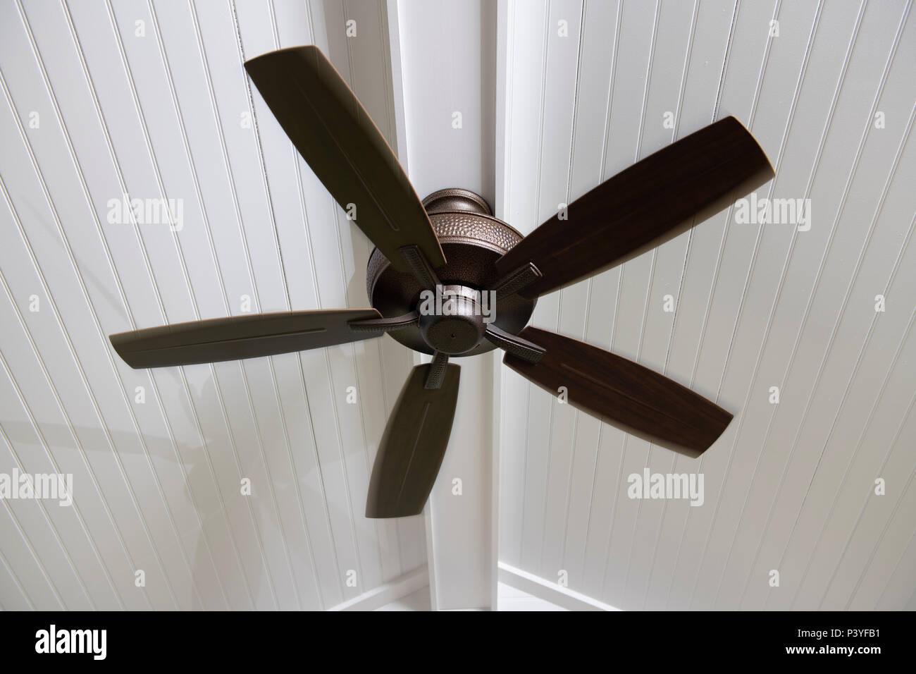 Un ventilador de techo eléctrico moderno en un proyectado en el porche para ayudar a enfriar el espacio en un día caliente Imagen De Stock