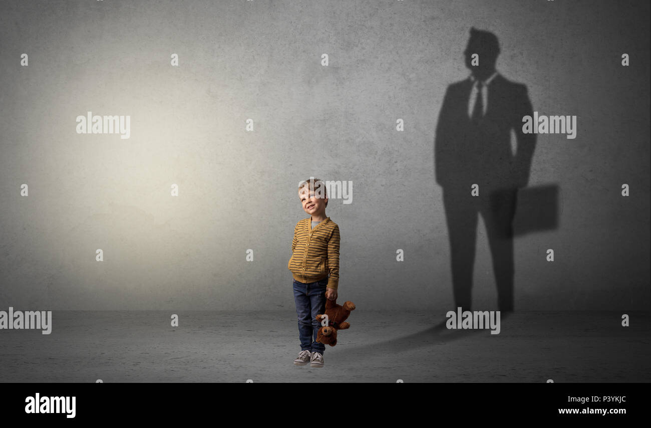 Little Boy imagine que va a ser empresario e ilustrando su futuro en una gran sombra Foto de stock
