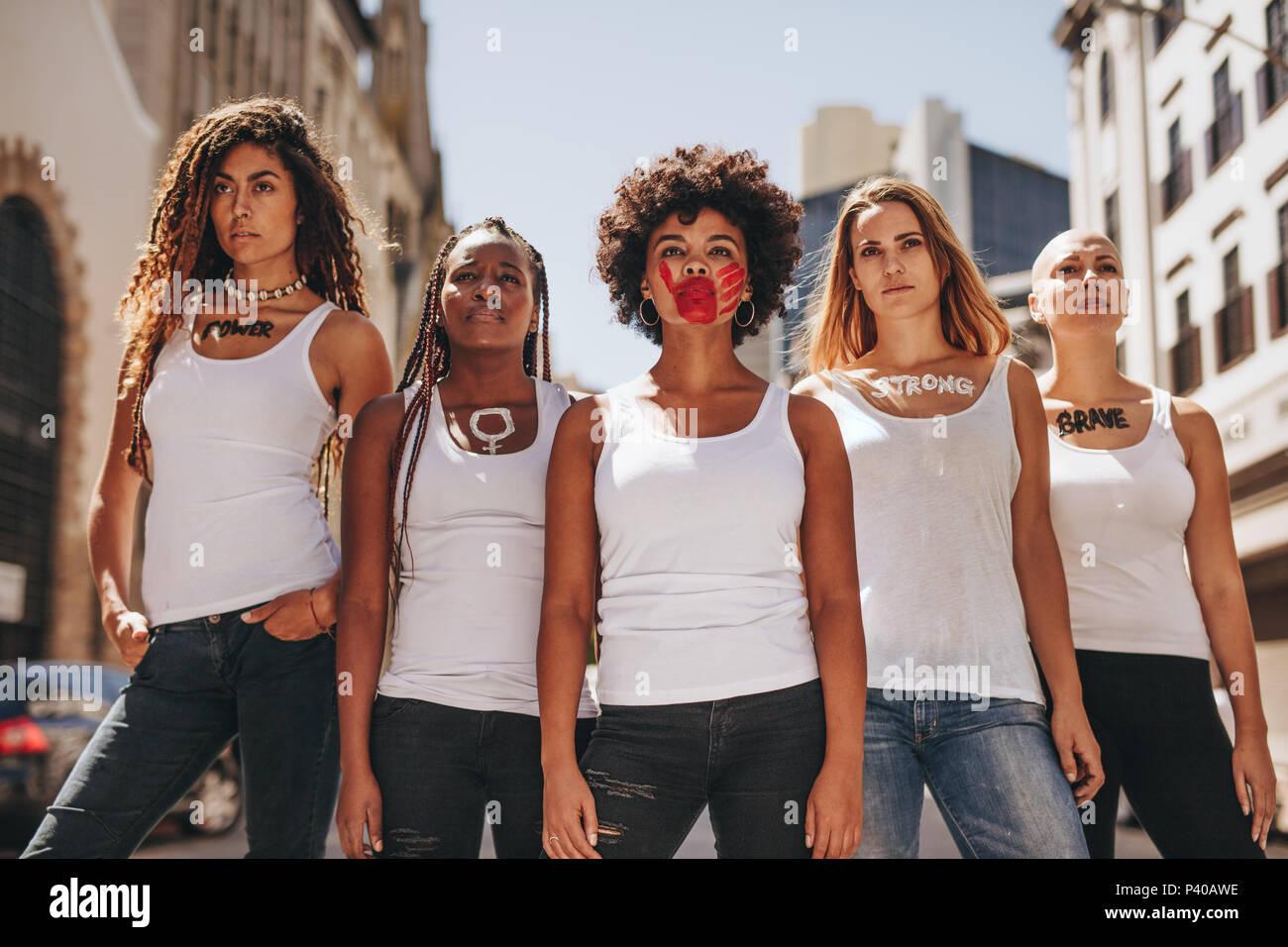 Grupo de mujeres manifestantes marzo en el camino para la emancipación de la mujer. Las mujeres activistas en código de vestir demostrando afuera. Imagen De Stock