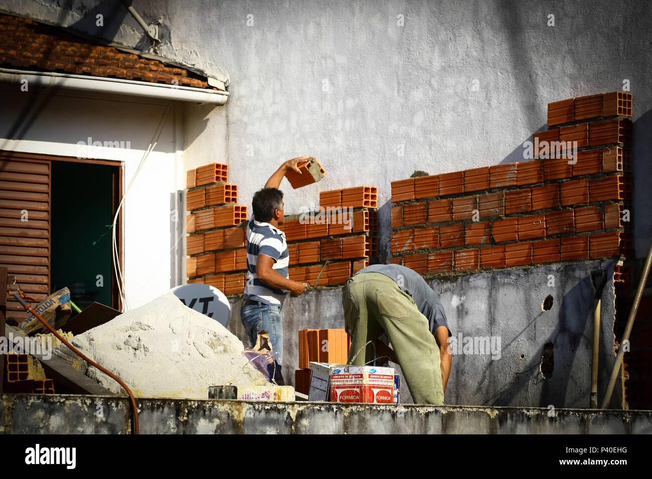 Em construção Pedreiros levantando parede de tijolos. Foto de stock