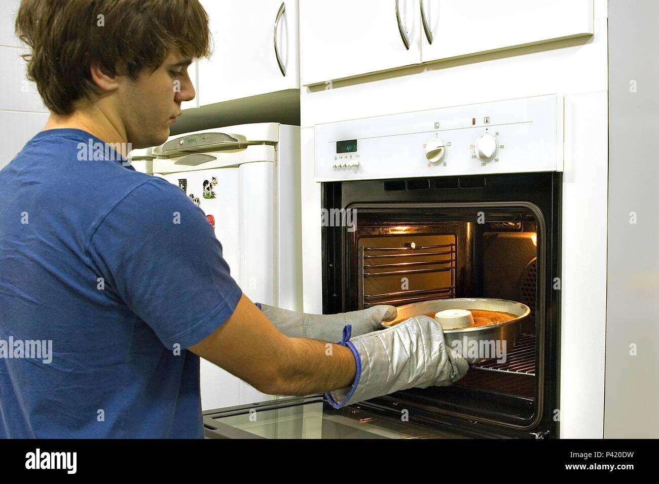 Jovem Masculino tirando el bolo do forno Bolo Bolo saindo do forno Bolo quente Imagen De Stock