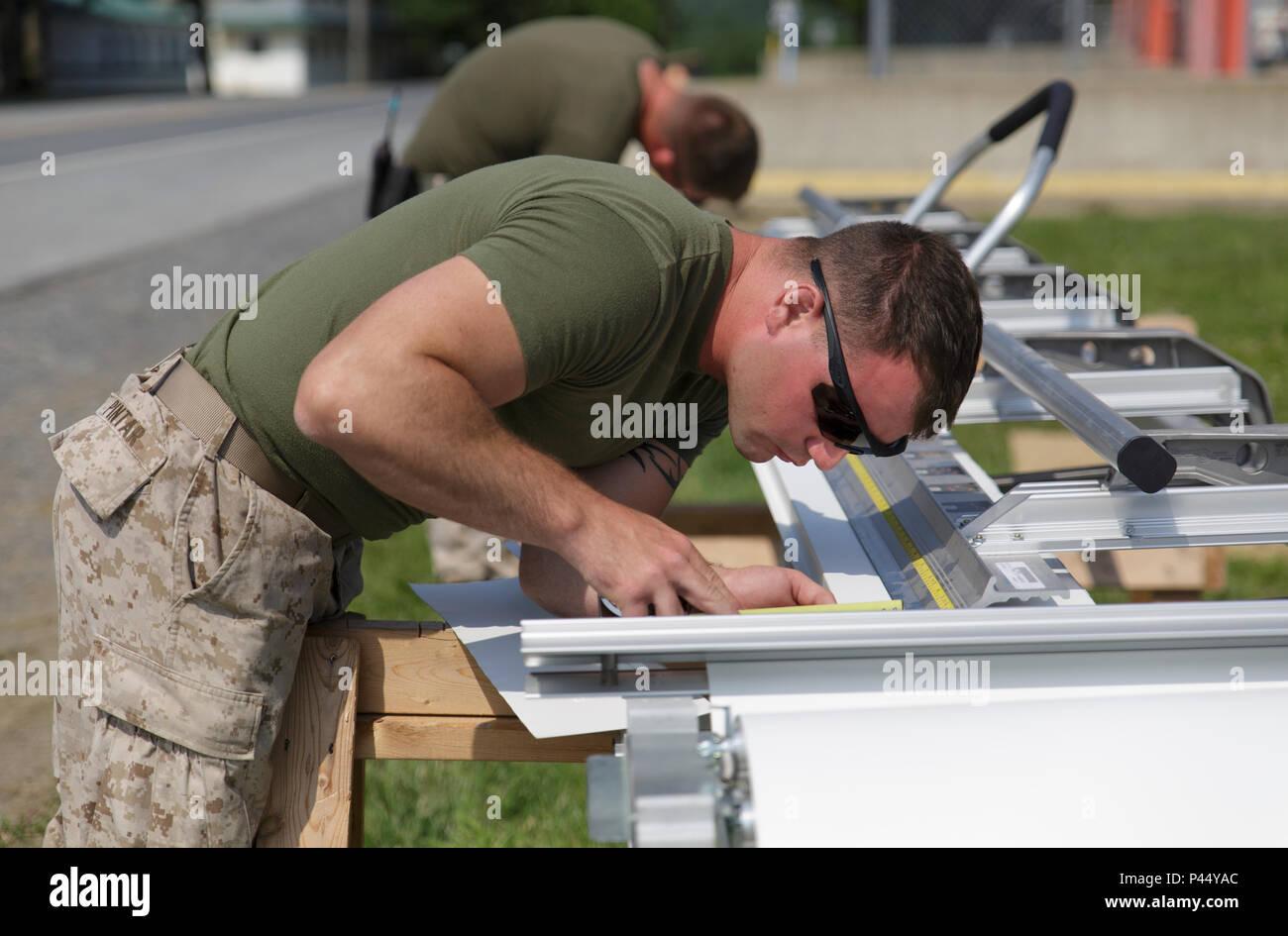 Lance Cpl. Benjamin M. Pintar, un ingeniero de combate con la compañía C, 6º, 4º Batallón de apoyo de ingenieros Marine Logistics Group, las fuerzas navales de reserva, toma las mediciones durante el proceso de creación de la fascia de aluminio revestido de un proyecto de renovación de los cuarteles durante el ejercicio Daga roja en Fort Indiantown Gap, Penn., 11 de junio de 2016. Como parte del ejercicio, los infantes de marina y los comandos británicos ha trabajado en diversos proyectos de renovación y construcción alrededor de la base del ejército. Ejercicio Daga roja es un ejercicio de capacitación bilateral Marines que le da una oportunidad para el intercambio de tácticas, técnicas y procedimientos, así como construir wo Imagen De Stock