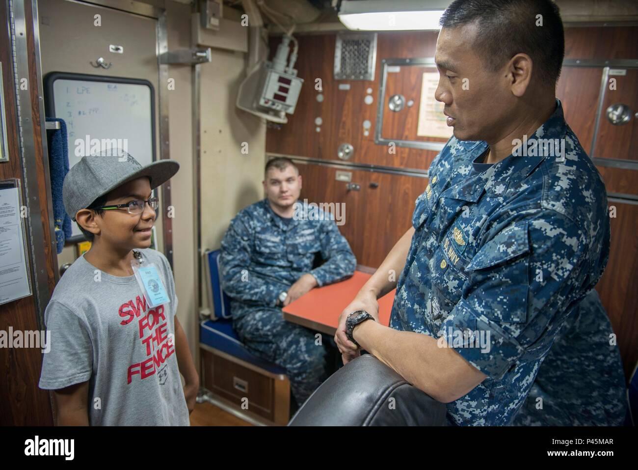 """BANGOR, Washington (Junio 28, 2016) - Cmdr. Melvyn Naidas, USS Louisiana (SSBN 743) Oro oficial comandante de la tripulación, habla con Hunter Smith, de la Sociedad de Leucemia y Linfoma de """"Chico del Año"""", durante una excursión de la clase Ohio de misiles balísticos en la Base Naval de submarinos Kitsap - Bangor. Smith, quien fue diagnosticado con leucemia linfoblástica aguda a la edad de dos años, fue declarado libre de cáncer en 2012 y aspira a convertirse en un marinero cuando crezca. (Ee.Uu. Navy photo by jefe especialista en comunicación de masas Kenneth G. Takada/liberado) Imagen De Stock"""