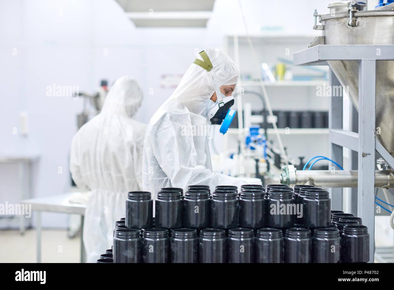 Los empleados que trabajan en la fábrica de ropa protectora Imagen De Stock