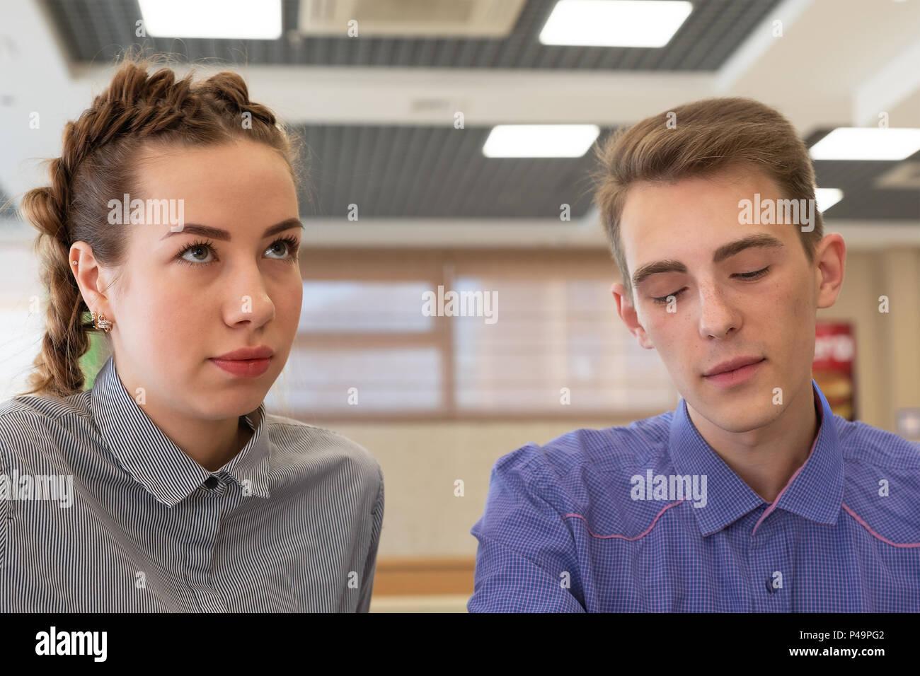 La chica y el chico sentarse cerca de rostros tristes. El chico miró hacia abajo en la parte inferior, y la chica se ve en la parte superior. Imagen De Stock
