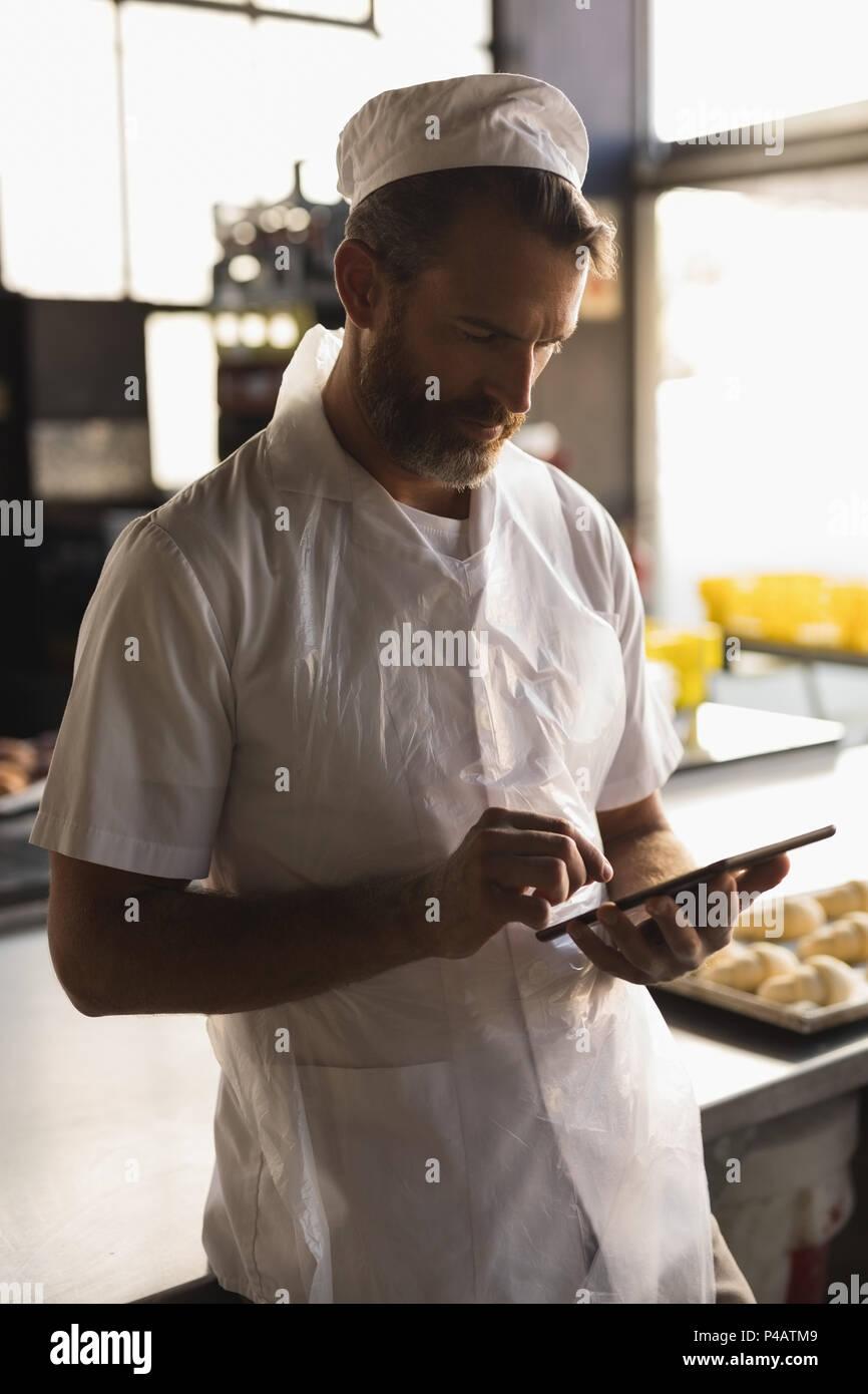 Baker macho utilizando tablet digital Imagen De Stock