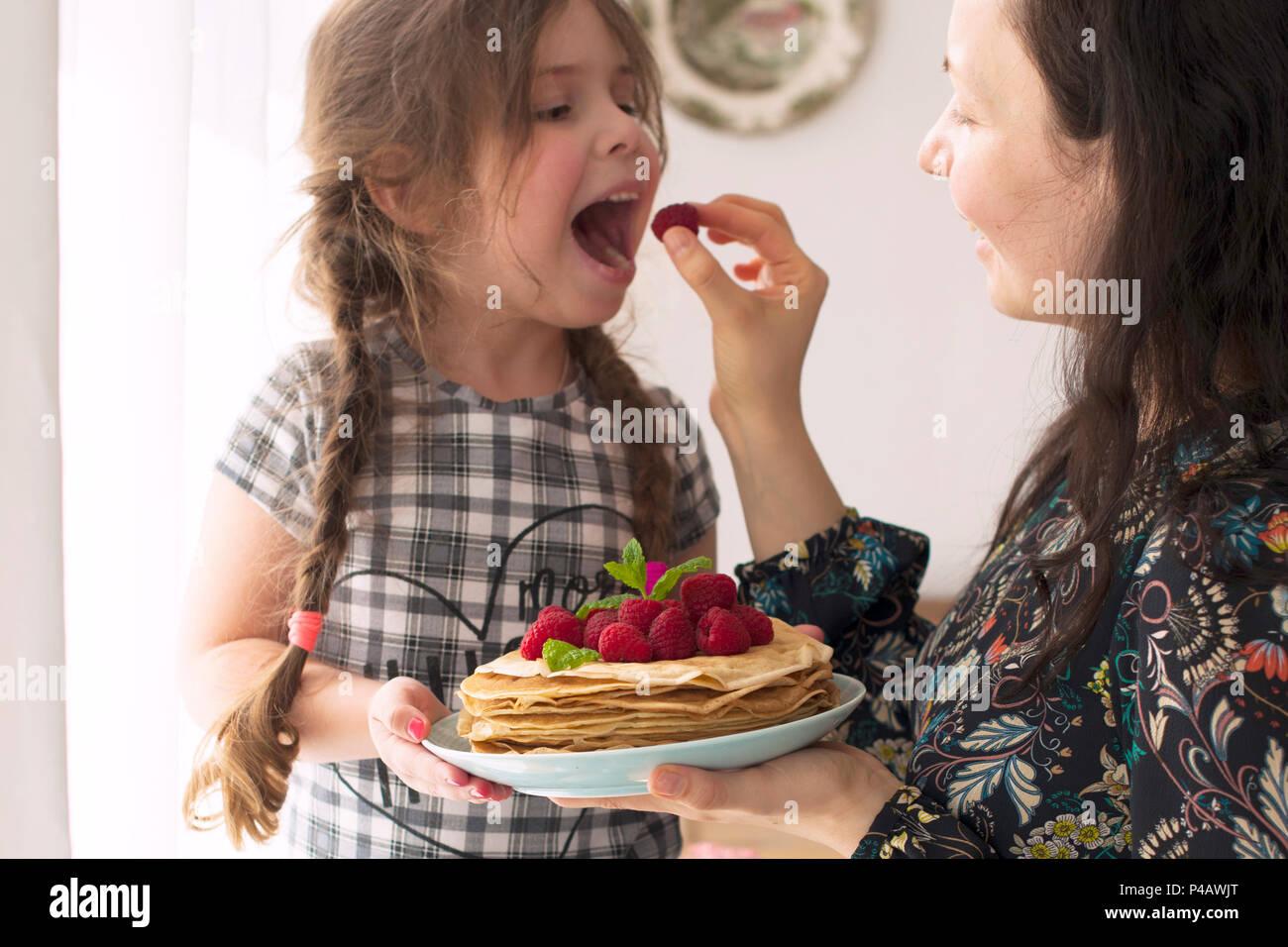 Mamá y la niña están sosteniendo un plato con tortitas caseras y bayas. Delicioso desayuno en casa. Una familia feliz. Buenos días, Imagen De Stock
