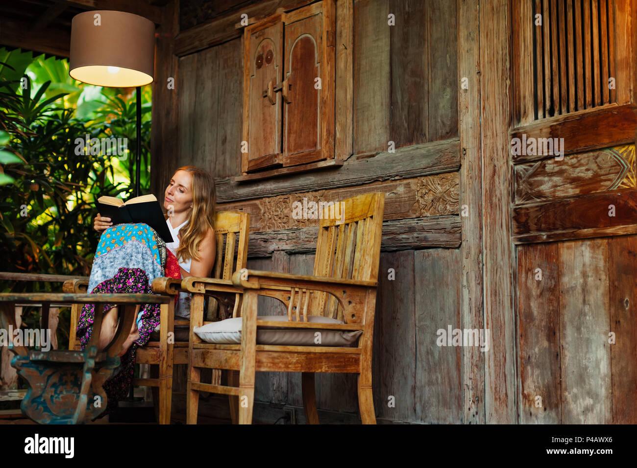 Atractiva chica sentarse en la terraza al aire libre del bungalow de madera con vista al jardín tropical, leer romance en libro de papel. Mujer joven relajándose en la villa de lujo Imagen De Stock