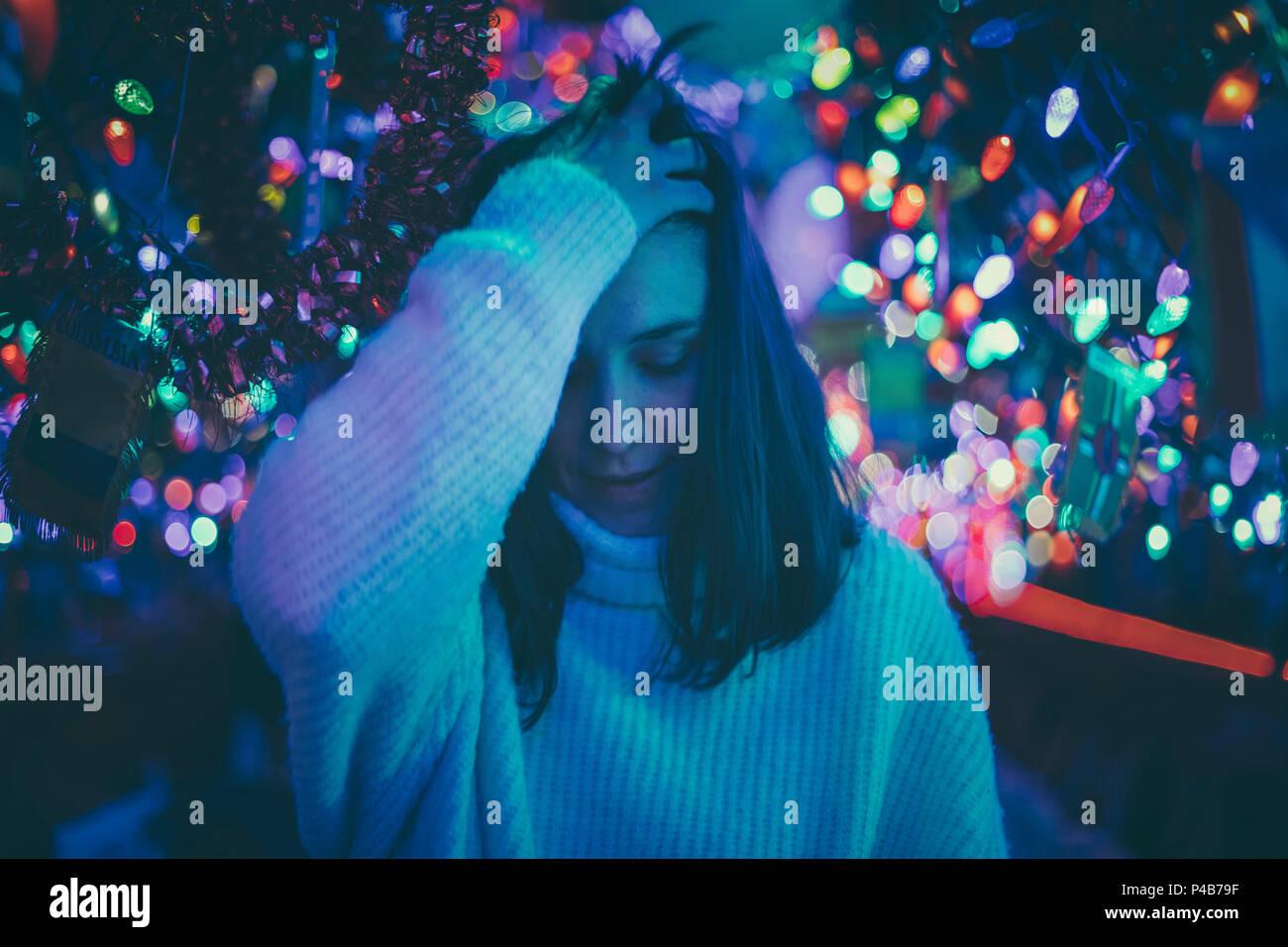 Mujer morena moviendo su cabello entre luces de Navidad Foto de stock