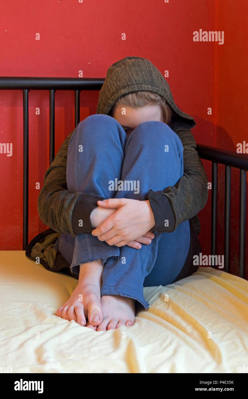 Chico perturbado sentada en su cama (la escena está siendo actuado) Imagen De Stock