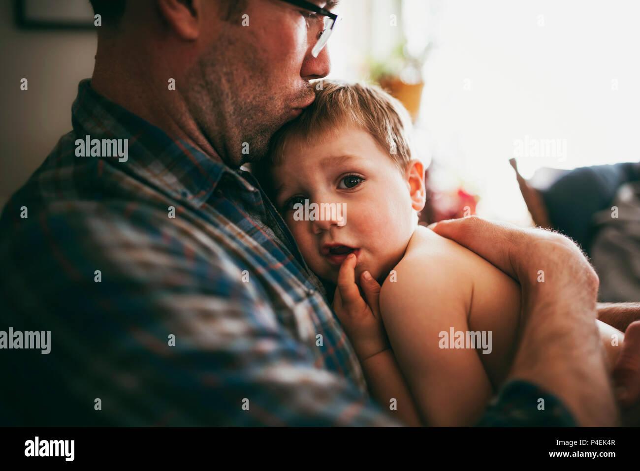 Padre sentado en el sofá abrazando a su hijo y le beso en la cabeza Foto de stock