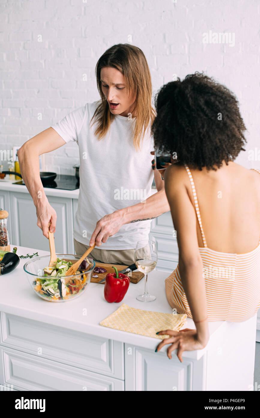 Vista trasera de la mujer dispara novio en el smartphone mientras él cocinar ensalada en la cocina Imagen De Stock