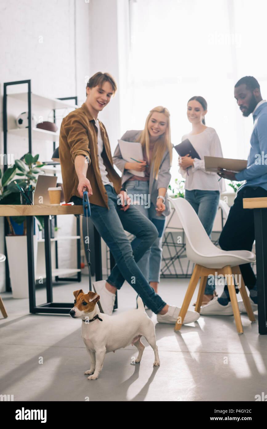 Los compañeros de negocio multiétnica sonriente con los libros de texto y Jack Russell terrier en correa en la oficina moderna Imagen De Stock