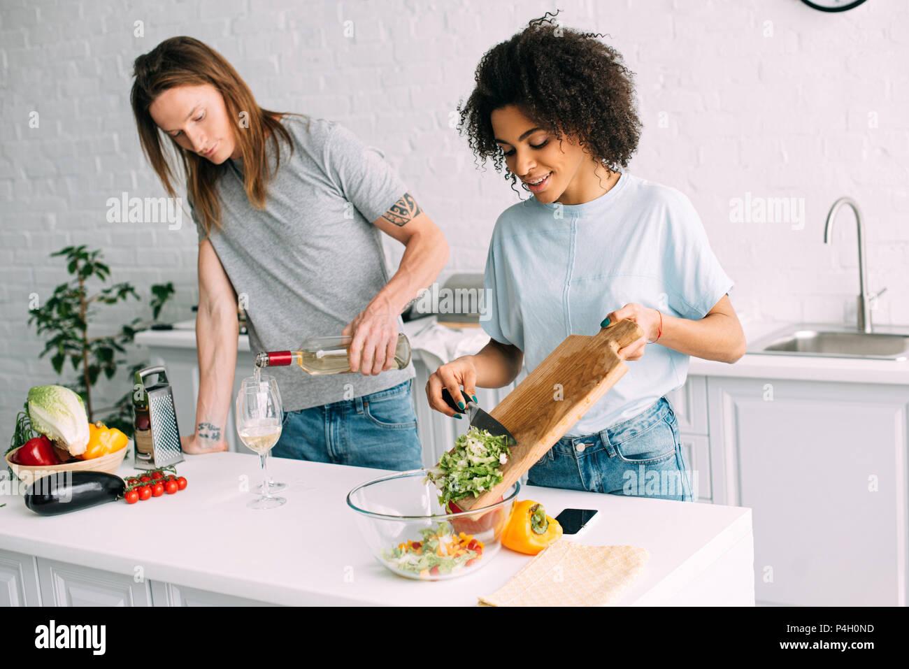 Joven afroamericana cocinar ensalada y novio verter en el vaso de vino blanco Imagen De Stock