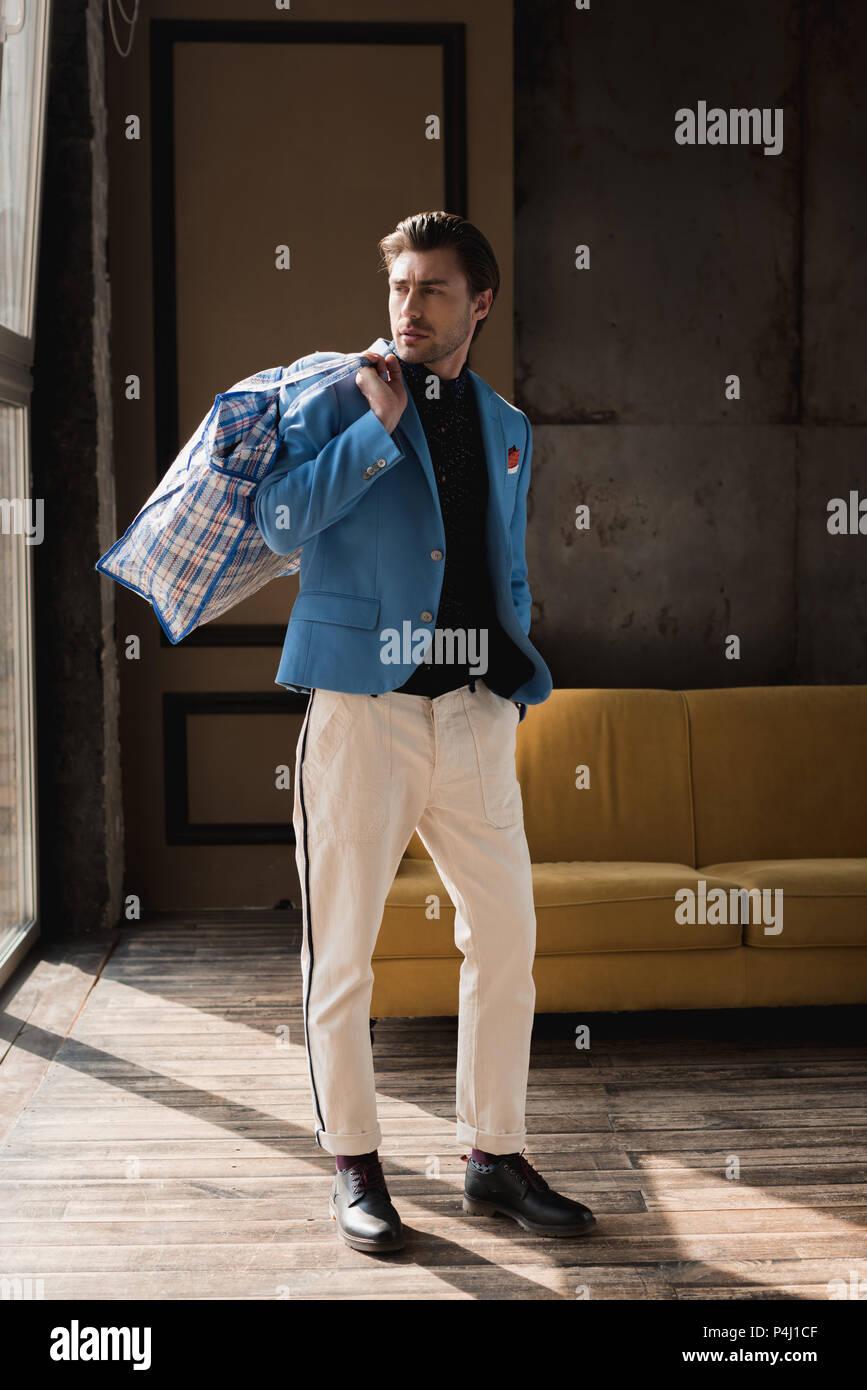 Apuesto joven con vintage bolsón con cremallera en el hombro en loft interior Imagen De Stock