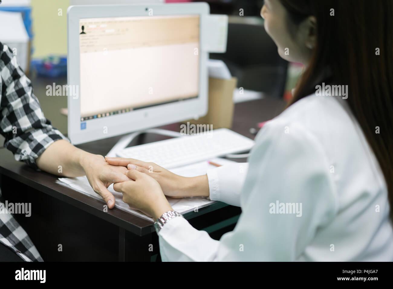 Amable doctora manos sosteniendo la mano del paciente sentado al escritorio de aliento, de empatía, vítores y apoyo al examen médico. Mala n Imagen De Stock