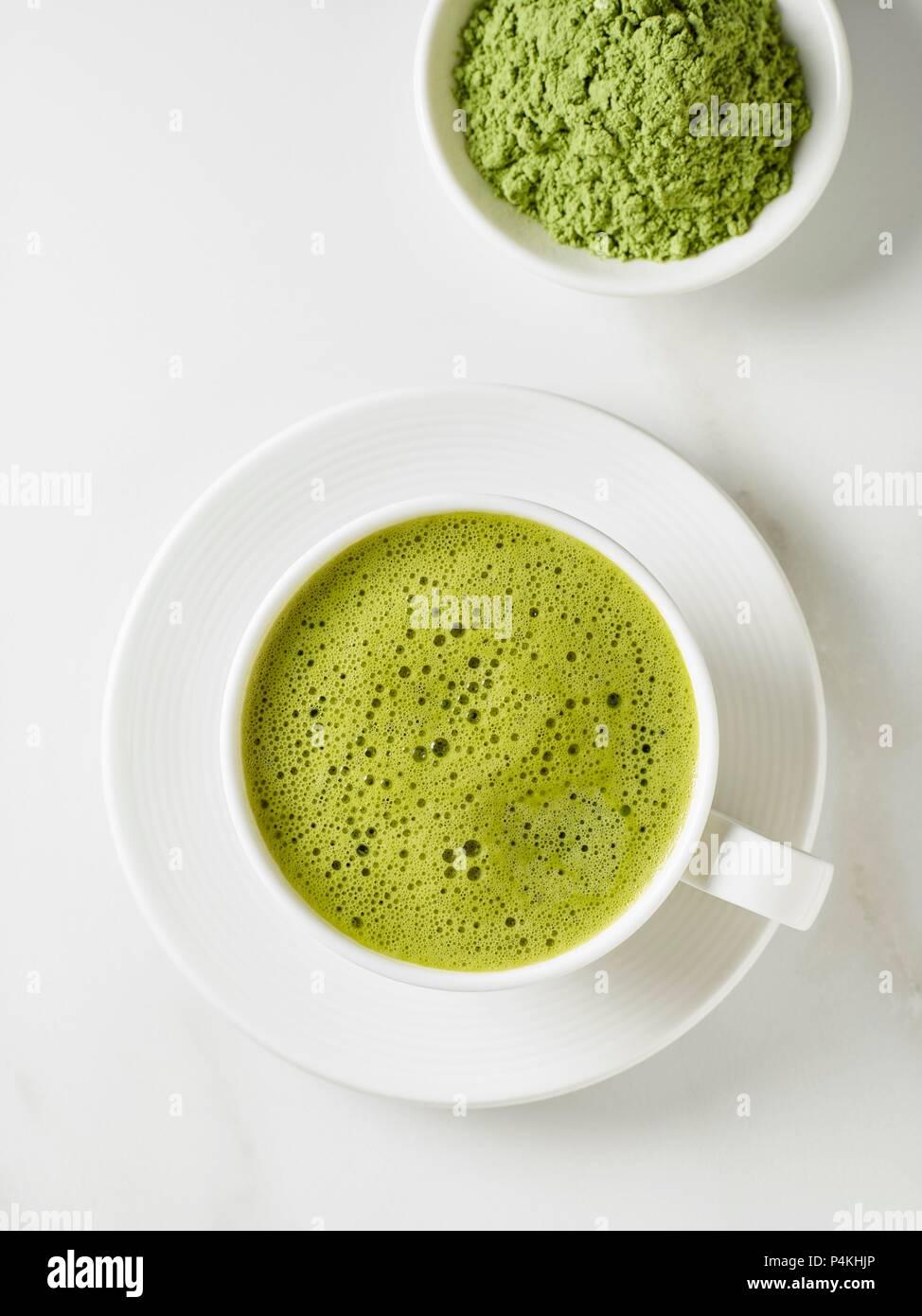 Una taza de té matcha y un tazón de polvo de té (ver arriba) Imagen De Stock