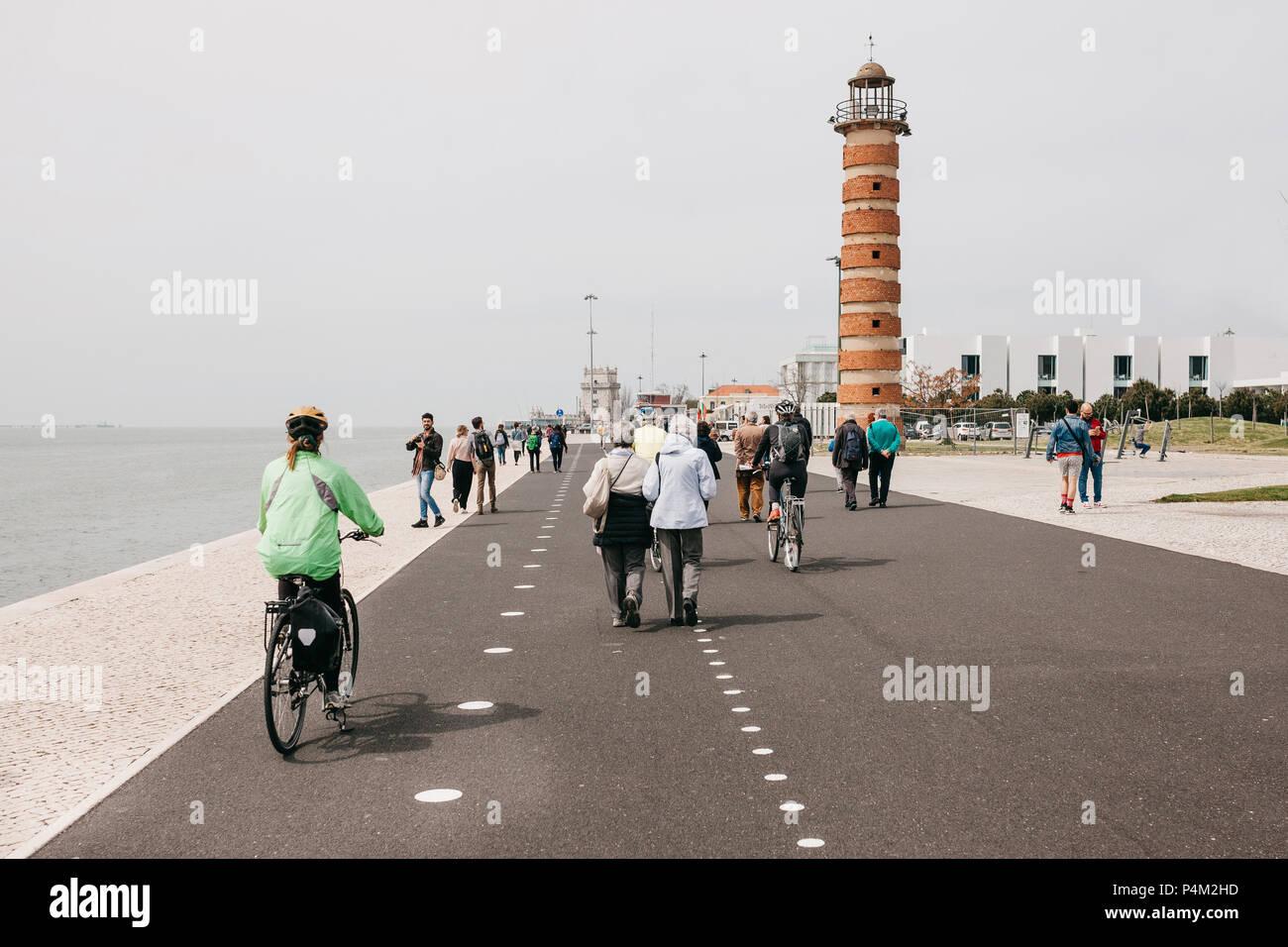 Lisboa, 18 de junio, 2018: la gente paseando por el paseo marítimo en la zona de Belem. Algunas personas ir en bicicleta. La vida en la ciudad ordinaria Foto de stock